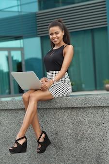 Czarna biznesowa kobieta siedzi w finansowym mieście, używając laptopa, zamyślony, słoneczny na zewnątrz.