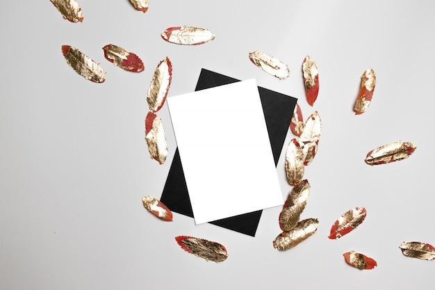 Czarna biznesowa koperta z białym papierem i złotem opuszcza na szarym tle. minimalistyczny styl