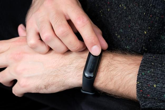 Czarna bransoletka fitness na zbliżenie dłoni faceta. nowoczesne gadżety sportowe i zdrowotne.