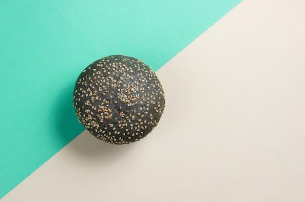 Czarna bułka z sezamem na pastelowym kolorowym tle.