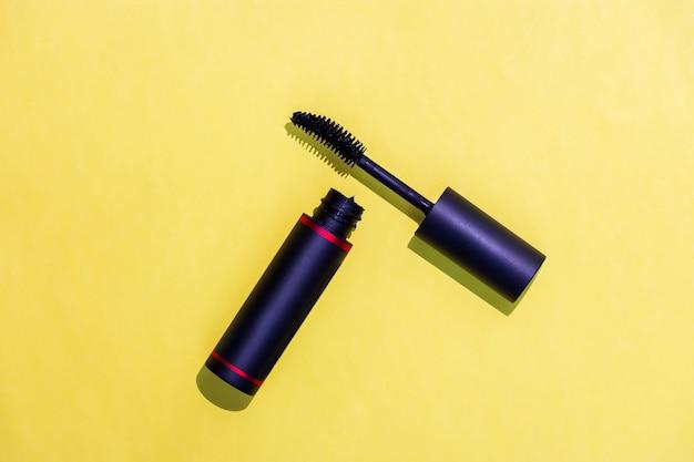 Czarna butelka tusz do rzęs i krzywa szczotka na białym tle żółty. koncepcja kosmetyków i mody.