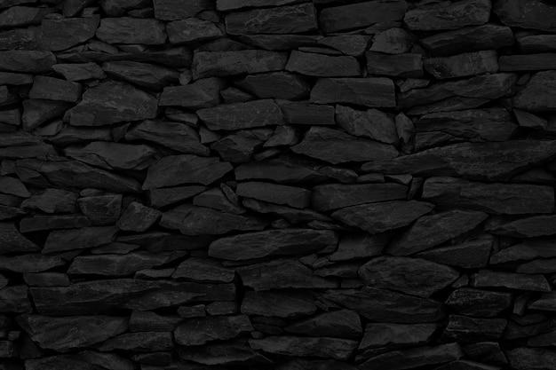 Czarna cegła kamienny mur tekstura tło ze starym wzorem w stylu brudne i vintage.