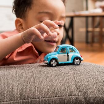 Czarna chłopiec bawić się z zabawkarskim samochodem