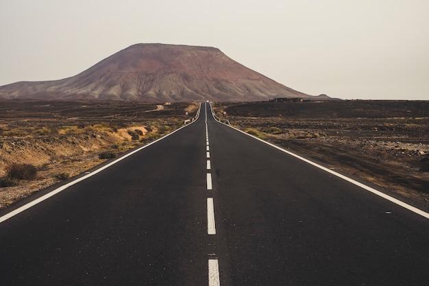 Czarna ciemna asfaltowa droga pośrodku pustyni i piaszczystych wydm