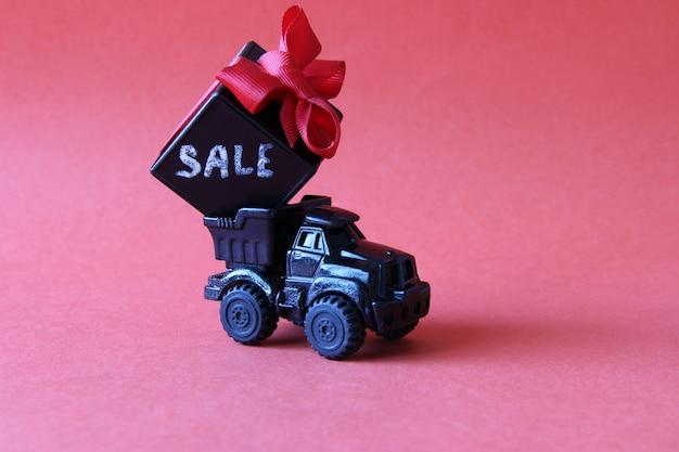 Czarna ciężarówka z pudełkiem upominkowym z kokardą i napisem rabaty na czerwonym tle