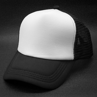 Czarna czapka i biała powierzchnia na ciemnym tle. modny kapelusz do projektowania.