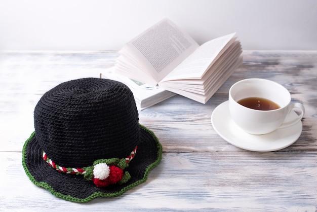 Czarna czapka z dzianiny w świąteczne dekoracje stoi na białym drewnianym stole z książkami i filiżanką herbaty.