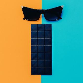 Czarna czekolada i stylowe okulary przeciwsłoneczne. minimalizm szczegóły sztuki mody