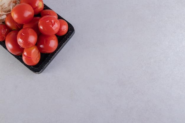 Czarna deska do krojenia marynowanych pomidorów i kapusty na kamieniu.