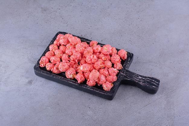 Czarna deska do krojenia różowych kulek popcornu na kamiennej powierzchni