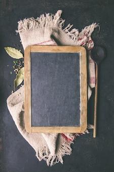 Czarna deska, drewniana łyżka i pikantność - kulinarny tło