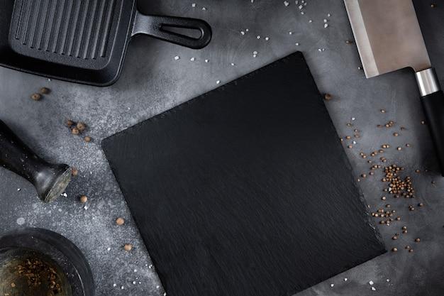 Czarna deska łupkowa z patelnią do grilla, nóż z przyprawami na szarym stole