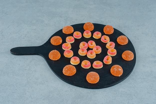 Czarna deska pełna okrągłych pomarańczowych cukierków galaretkowych w kształcie kółek i pomarańczowych galaretek z cukrem