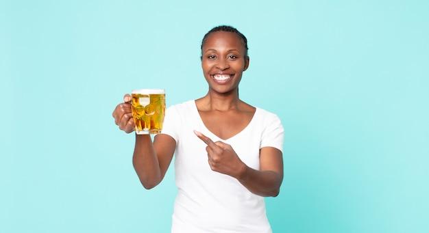 Czarna dorosła kobieta z afryki i trzymająca kufel piwa