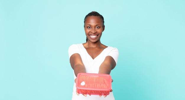 Czarna dorosła kobieta z afryki, trzymająca tupperware