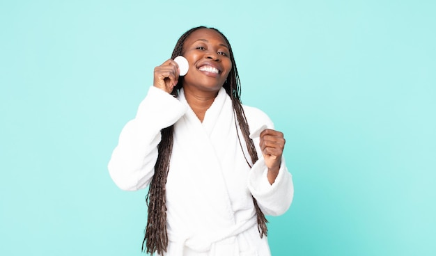 Czarna dorosła kobieta z afryki, ubrana w szlafrok i trzymająca bawełnę do czyszczenia twarzy