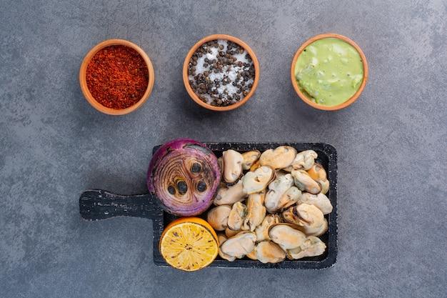 Czarna drewniana deska gotowanych muszelek ze smażoną cebulą i plasterkami cytryny na kamiennym tle.