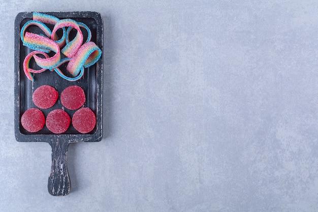 Czarna drewniana deska pełna słodkich kolorowych cukierków.