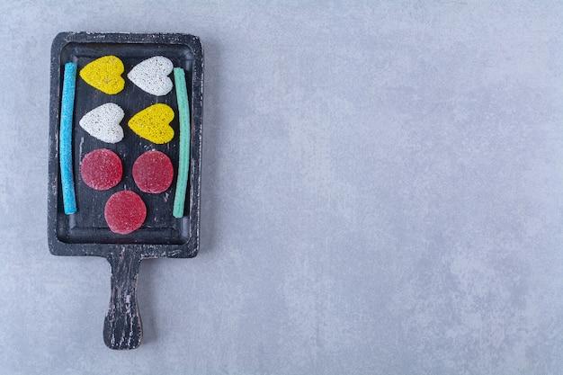 Czarna drewniana deska pełna słodkich kolorowych cukierków