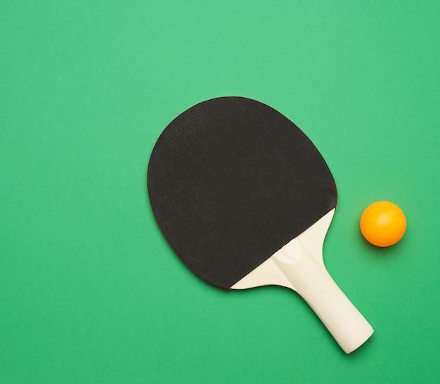 Czarna drewniana rakieta i plastikowa pomarańczowa piłka do tenisa stołowego, widok z góry