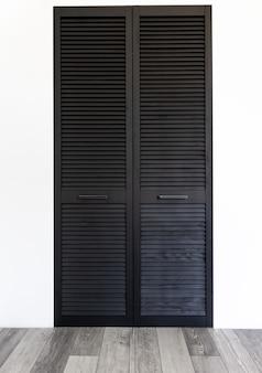 Czarna drewniana szafa ozdobiona roletami, szafa z dekoracją rolet.