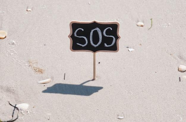 Czarna drewniana tablica z napisem sos