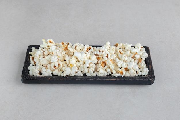 Czarna drewniana taca ze świeżym popcornem na marmurowym stole.