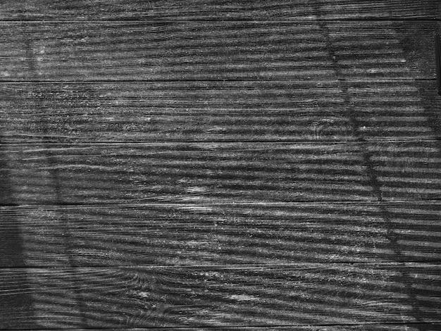 Czarna drewniana tekstura ze światłem z okna przez rolety