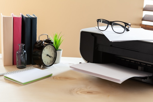 Czarna drukarka na stole z budzikiem i książkami