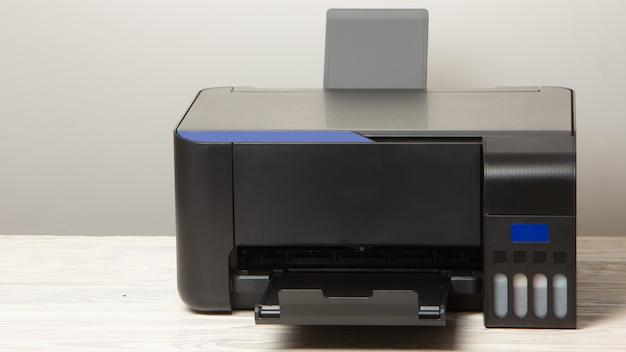 Czarna drukarka ze skanerem, na białym drewnianym stole.
