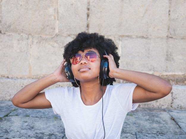 Czarna dziewczyna, słuchanie muzyki w słuchawkach, na ulicy, na białym tle