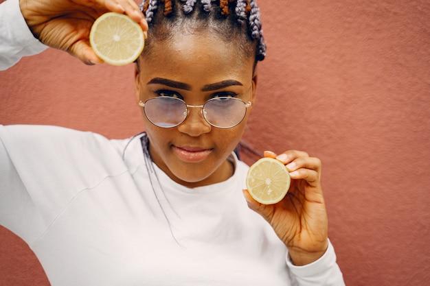 Czarna dziewczyna stojąca na ścianie backgroung z cytrynami