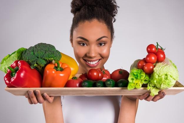 Czarna Dziewczyna Trzyma Tacę Z Warzywami Odizolowywającymi. Premium Zdjęcia