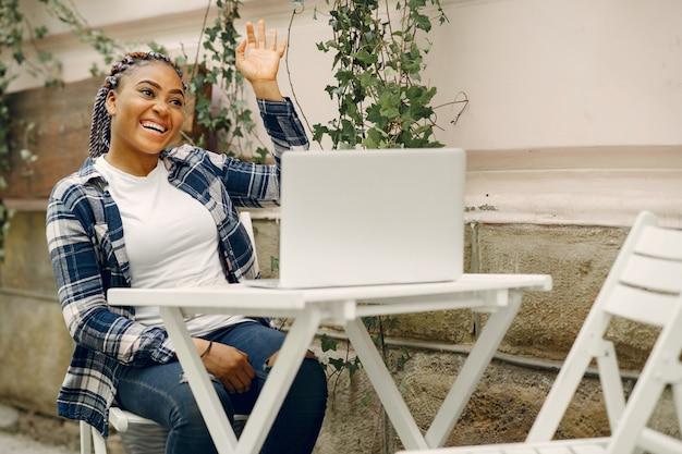 Czarna dziewczyna w letnim mieście z laptopem