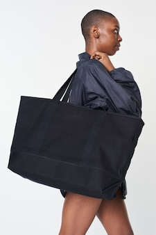 Czarna dziewczyna z czarną, obszerną, pustą torbą na zakupy