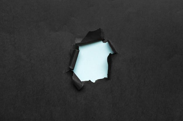 Czarna dziura w papierze z poszarpanymi bokami.