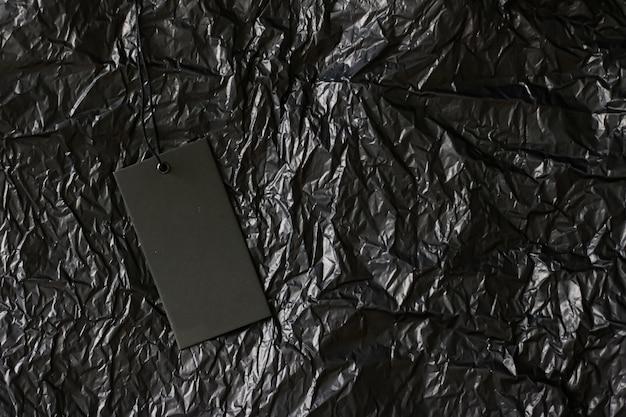 Czarna etykieta na ciemnym tle z koncepcją zrównoważonej mody i marki copyspace