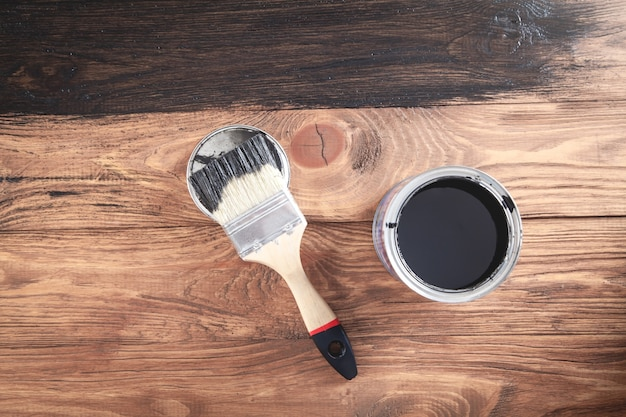 Czarna farba i pędzel na drewnianym tle malowanie desek