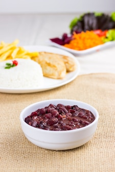 Czarna fasola na białym talerzu na ręczniku z surowej bawełny z pełnym talerzem z kurczakiem ryżowym i frytkami w tyle