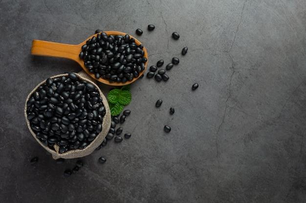 Czarna fasola w małej drewnianej łyżeczce umieść obok worka pełnego czarnej fasoli