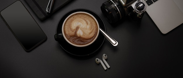Czarna filiżanka kawy na ciemnym stole roboczym z laptopem, aparatem, książką terminarza i urządzeniami cyfrowymi