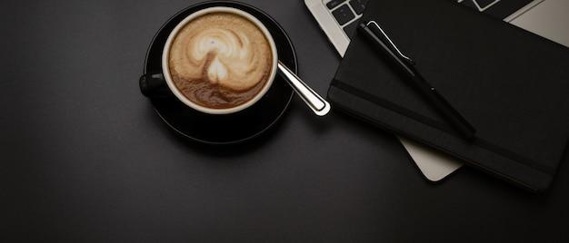 Czarna filiżanka kawy na ciemnym stole roboczym z laptopem, rozkładem książek, długopisem i kopią