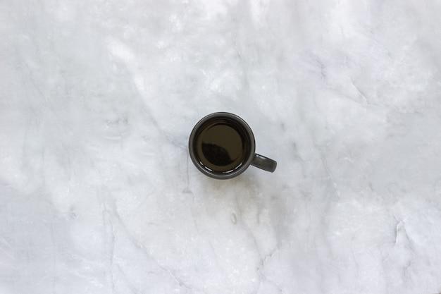 Czarna filiżanka kawy na marmurowym stołowym tle.