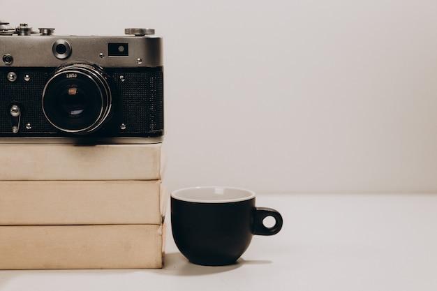 Czarna filiżanka kawy ze starą kamerą i białymi książkami