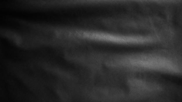 Czarna flaga z tkaniny tekstylnej, abstrakcyjne tło z miękkimi falami, tło draperia z nastrojem miękkości i tonem.