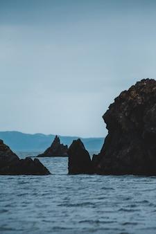 Czarna formacja skalna na morzu pod białym niebem w ciągu dnia