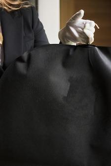 Czarna garniturowa torba podróżna ręce pracownika hotelu w białych rękawiczkach