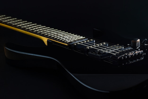 Czarna gitara elektryczna w ciemności.