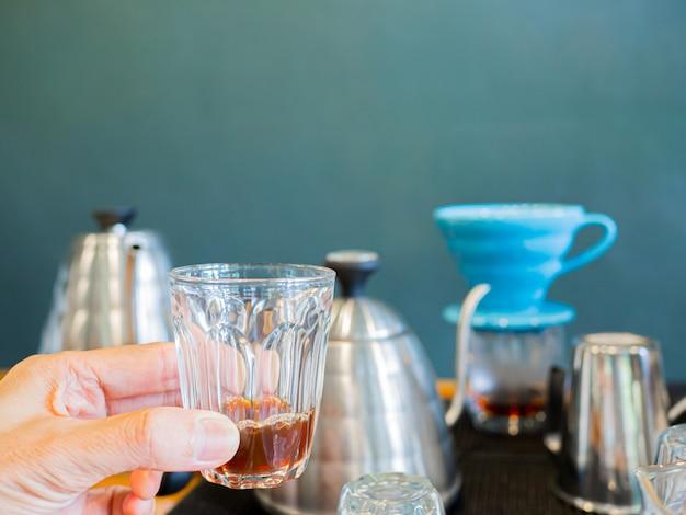 Czarna gorąca kawa jest wydobywana z procesu kroplówki w dłoni espresso trzymanej przez mężczyznę.