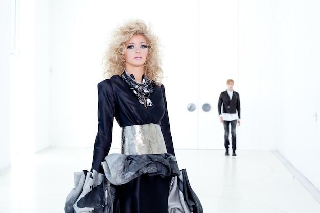 Czarna haute couture retro futurysta para w nowoczesnej białej sali z wampirem inspiracji